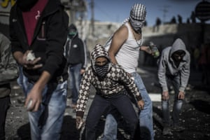 Palestinian youths take cover during clashes with Israeli border police in the Shuafat refugee camp following Friday prayers