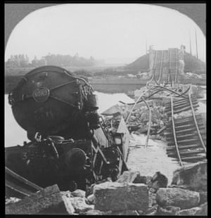 A Red Cross train lies half-submerged in water after a United States Marine bridge was blown up by German forces during World War I. The iron rails of the track are twisted among the rocks and rubble.