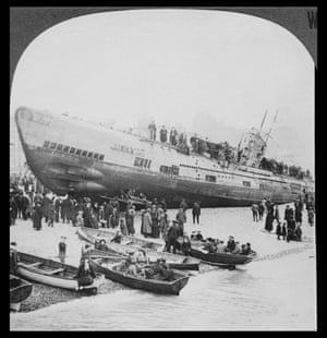 Citizens of a south England coastal town walk on and around a German U-boat left stranded on shore after the end of the war. Large groups of people walk along the boat deck while inspecting the large vessel.