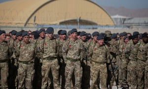 Remembrance poppies adorn uniforms as British troops and service personal remaining in Afghanistan are joined by International Security Assistance Force (ISAF) personnel and civilians as they gather for a Remembrance Sunday service at Kandahar Airfield.