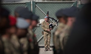 A piper plays as British troops and service personal remaining in Afghanistan are joined by International Security Assistance Force (ISAF) personnel and civilians as they gather for a Remembrance Sunday service at Kandahar Airfield.