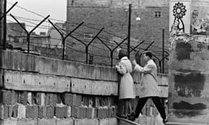 Couple peers over berlin wall 1961