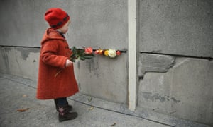 Hulda, 3, places flowers in between slats of the former Berlin Wall at the Berlin Wall Memorial at Bernauer Strasse.