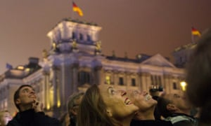 People watch balloons marking the former border flying away in front of the Reichstag building.