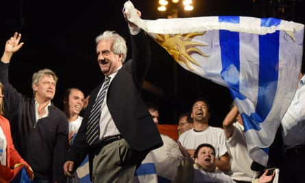 Tabare Vazquez  waves an Uruguayan flag to celebrate his victory