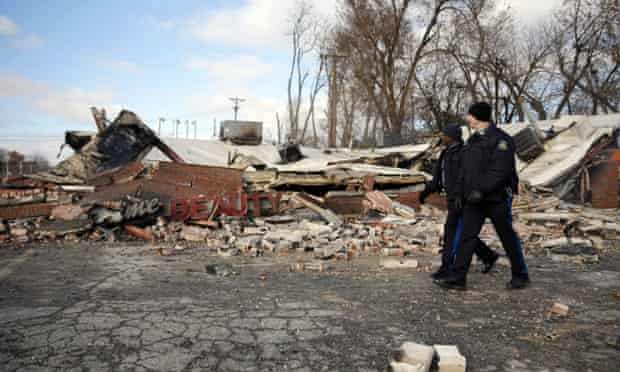 Members of the Missouri Highway Patrol walk past a building burned to the ground in Ferguson.