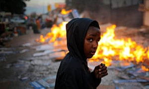 Boy walks past fire keeping evicted families warm