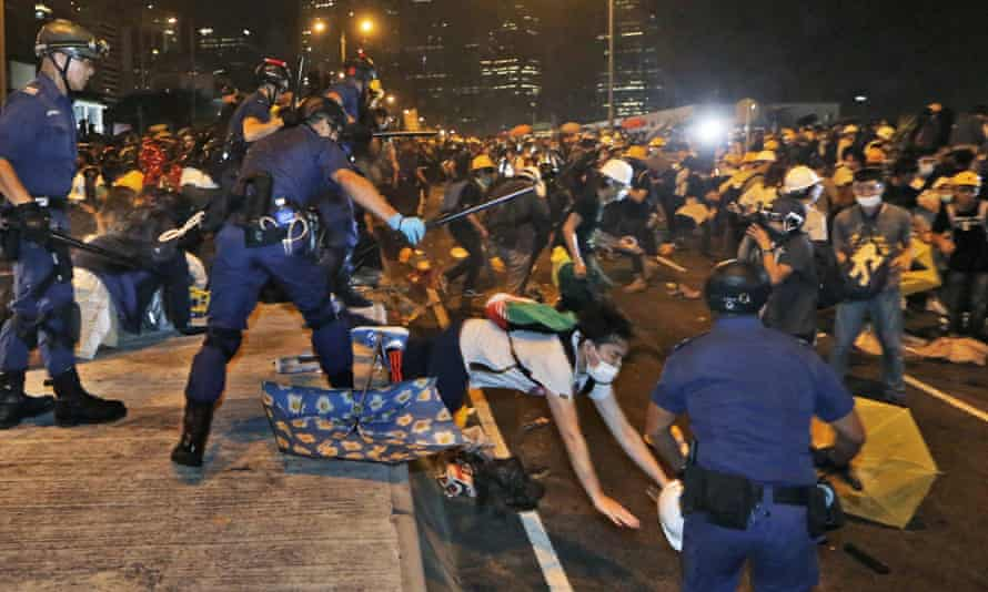 Police officers throw a pro-democracy protester on the main road outside government headquarters,