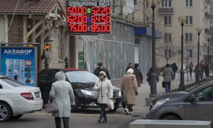 People walk past a display with currency exchange rates in central Moscow, Monday, Dec. 1, 2014.