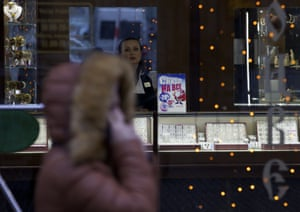 "A saleswoman waits for customers in a jewerly shop with a poster reading ""Sales on everything"" in downtown Moscow, Russia, Monday, Dec. 01, 2014."