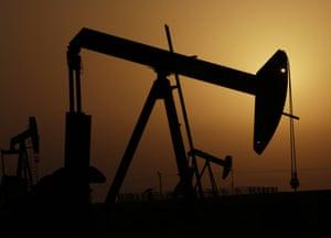 Oil pumps work at sunset in the desert oil fields of Sakhir, Bahrain, Tuesday, Oct. 14, 2014.