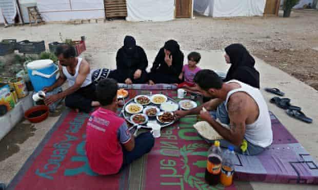 Syrian refugees eating at a refugee camp in Marj