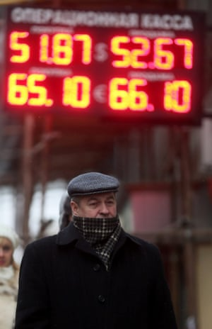 A Russian man passes electronic information panels displaying currency exchange rates in Moscow, Russia, 01 December 2014.