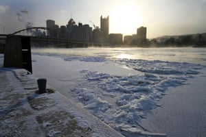 The sun rises over the skyline of Pittsburgh and a frozen Allegheny river