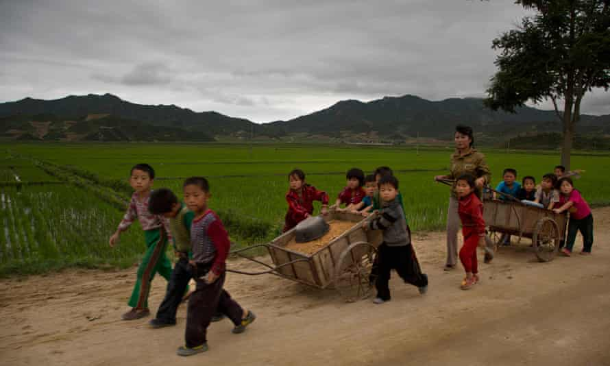 Schoolchildren help to fix potholes in a rural road in North Korea's North Hamgyong province. Outside the capital, most remain deep in poverty.