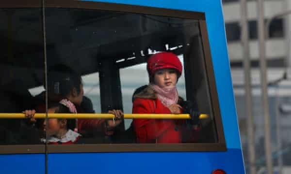 A woman framed a bus window in Pyongyang.