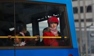 A woman framed a bus window in Pyongyang.