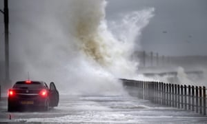 A car drives along Seaview road as waves crash over in Saltcoats, Scotland.