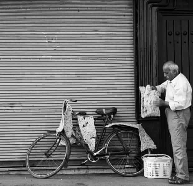 An Iranian man folds sangak bread.
