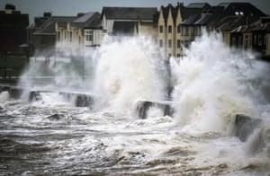 Waves crash over the promenade wall in Prestwick, Scotland