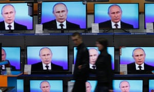 Muscovites walk past TV sets during Russian President Vladimir Putin's annual nationwide phone-in.