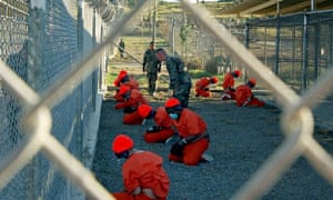 Detainees in orange jumpsuits sit in a holding area at Guantanamo Bay, Cuba