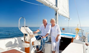 DE3TRN A happy senior couple sitting at the wheel of a sail boat on a calm blue