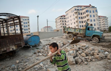 A boy helps make bricks for new apartment blocks next to Aria City, a gated high-end residential complex.