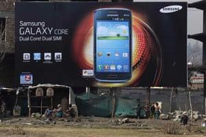 Afghan vendors sit under an advertising billboard in Kabul.