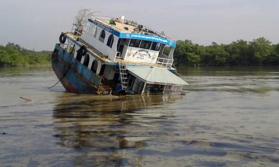 """In this photograph taken on December 9, 2014, a Bangladeshi oil-tanker lies half-submerged after it was hit by a cargo vessel on the Shela River in the Sundarbans in Mongla. Bangladesh officials warned December 11 that an oil spill from a crashed tanker is threatening endangered dolphins and other wildlife in the massive Sundarbans mangrove region, branding the leak an ecological """"catastrophe""""."""