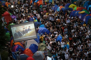 21 October Pro-democracy protesters watch formal talks between student protest leaders and government officials on a video screen near the government headquarters