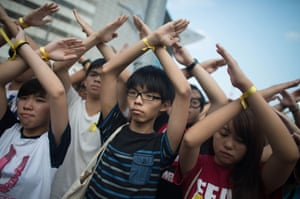 1 October Joshua Wong, centre, makes a gesture at a flag-raising ceremony at Golden Bauhinia Square. The protest leaders set a 1 October deadline for their demands to be met, calling for open elections and the resignation of Hong Kong's chief executive Leung Chun-ying