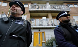Police stand guard at a property in Brixton