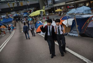 13 November School boys walk through the camp of pro-democracy supporters at the Admiralty protest site. Hong Kong's high court has authorised police to arrest protesters who obstruct bailiffs on the three interim restraining orders