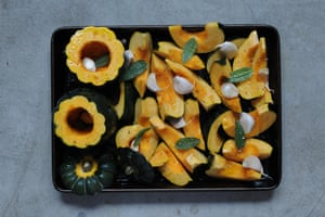 Acorn squash scattered with sage leaves and garlic ready to be roasted.