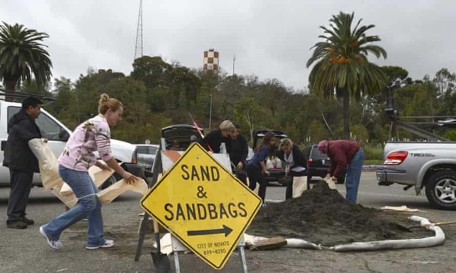 People fill sandbags during storm preparation outside the Hamilton Theater in Novato, California.