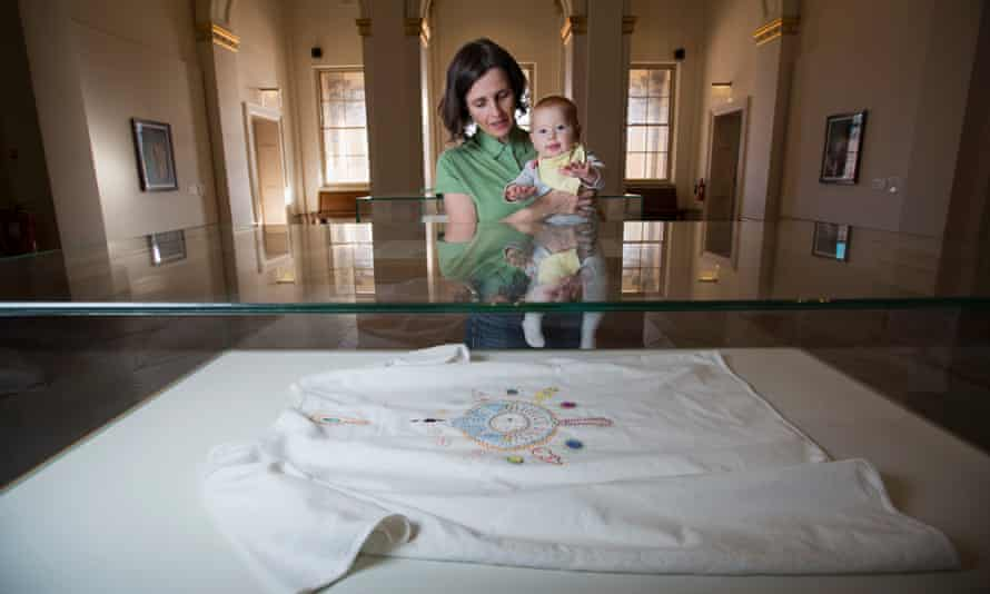 Tabitha Moses and her daughter, Gilda at the Walker Art Gallery, Liverpool. The exhibit in the case is a hospital gown embroidered with symbols of her IVF experience.