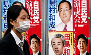 A woman passes election posters in Tokyo, with the prime minister, Shinzo Abe, bottom right. Only 12