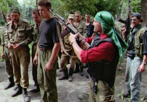A Chechen fighter points his rifle to the head of a Russian prisoner of war outside Grozny in August 1996.