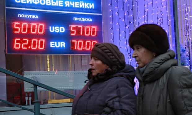 Muscovites pass a bureau de change. The rouble has sunk by more than 40% this year.