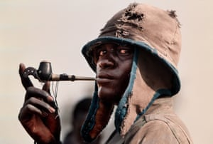 Madut Atien, an SPLA rebel, smokes a pipe after arriving to protect the peace village at Wunlit, Sudan. The SPLA  provided security for the peace conference conference between the Nuer & Dinka tribes