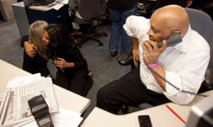 Washington Post director of photography Michel du Cille, right, talks on the phone as Carol Guzy and Nikki Kahn celebrate in the newsroom after finding out that Guzy, Kahn and Carioti won the Pulitzer Prize for Breaking News Photography for their images in Haiti after the catastrophic earthquake