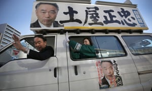 Masatada Tsuchiya, the ruling Liberal Democratic party candidate for a Tokyo district, waves from his election campaign car
