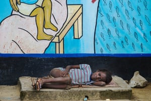 A sick child that health workers called Cynthia, lay on the a concrete rise as waited for  Liberian Health workers to remove dead bodies before she could enter the Redemption Hospital