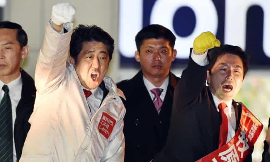 Shinzo Abe (in white coat) at a rally in Tokyo during his election campaign.