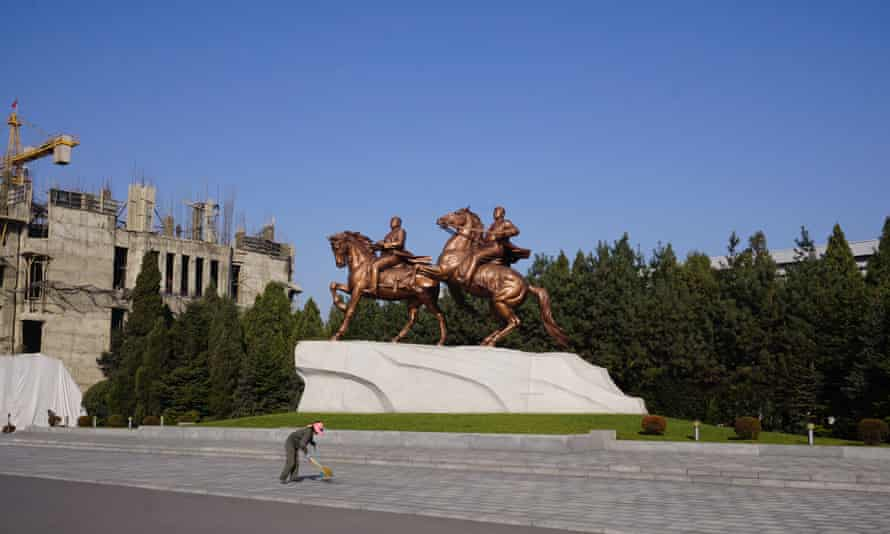 A woman sweeps the street in front of statues of Kim Il-sung and Kim Jong-il at the Mansudae Art Studio in Pyongyang. North Korea