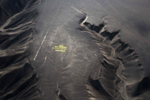 """Greenpeace activists stand next to massive letters delivering the message """"Time for Change: The Future is Renewable,"""" next to the hummingbird geoglyph in Nazca in Peru, Monday, Dec. 8, 2014. Greenpeace activists from Brazil, Argentina, Chile, Spain, Germany, Italy and Austria displayed the message, which can be viewed from the sky, during the climate talks in Peru, to honor the Nazca people, whose ancient geoglyphs are one of the country's cultural landmarks."""
