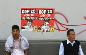"""Two men stand in front of a poster that reads in Spanish """"COP20, nest of predators,"""" during a march in """"Defense of Mother Earth"""" in Lima, Peru, Wednesday, Dec. 10, 2014. Thousands marched in support of Mother Earth as they chanted slogans against illegal mining, and logging operations, as well as oil drilling."""