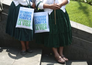 """Two Indian women from the Andes rest with their bags with messages in spanish that read, """" To defend the earth is to defend life"""" during a march in """"Defense of Mother Earth"""" in Lima, Peru, Wednesday, Dec. 10, 2014. Thousands marched in support of Mother Earth as they chanted slogans against illegal mining, and logging operations, as well as oil drilling. They asked that the exploitation of resources in their ancestral lands be stopped immediately. ("""