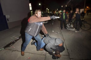 An undercover police officer, caught posing as a protester against police violence in Oakland, California, points his gun at the crowd after his partner is attacked. Police said more than 100 protesters marched in neighbouring Berkeley over the grand jury decisions not to indict white officers for the deaths of two unarmed black men